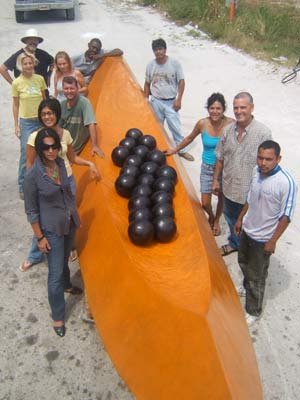 Bronze papaya, surrounded by foundry employees.